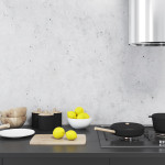 Concrete wall kitchen interior with a black countertop, a cutting board and a bowl of lemons near a cooker. Concept of home made food. 3d rendering mock up