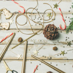 Getting ready for Christmas or New Year celebration party. Flat-lay pattern of holiday decoration objects, toys, candles, candy canes, tree branches on white background, top view, wide composition