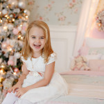 Very nice charming little girl blonde in white dress sitting on a child's bed and laughs loudly on the background of Christmas trees in bright interior of the house