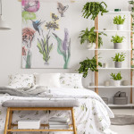 Real photo of white bedroom interior with many fresh plants, king-size bed, material painting with floral pattern and bench with books