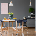 Grey dining room interior with pink and blue painting, wooden table and chest of drawers