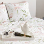 Close-up of a blurred tray with a pot, cup and bouquet of flowers on a double bed in a bedroom interior