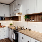 Stylish kitchen interior design. Luxury modern kitchen furniture in grey color and steel oven,fridge, sink, wooden tabletop, pots,. Gray cabinets in scandinavian style. Home renovation.