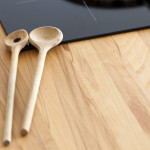 Two Cooking Spoon lies on Worktop nearby Ceramic Hob with Copy Space in the lower Area of the Image