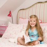 Young girl sitting on bed with book smiling