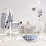 Bright and clean room for a newborn, with a wire armchair in the foreground and white baby room furniture