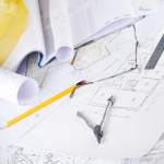 Yellow helmet and heap of project drawings